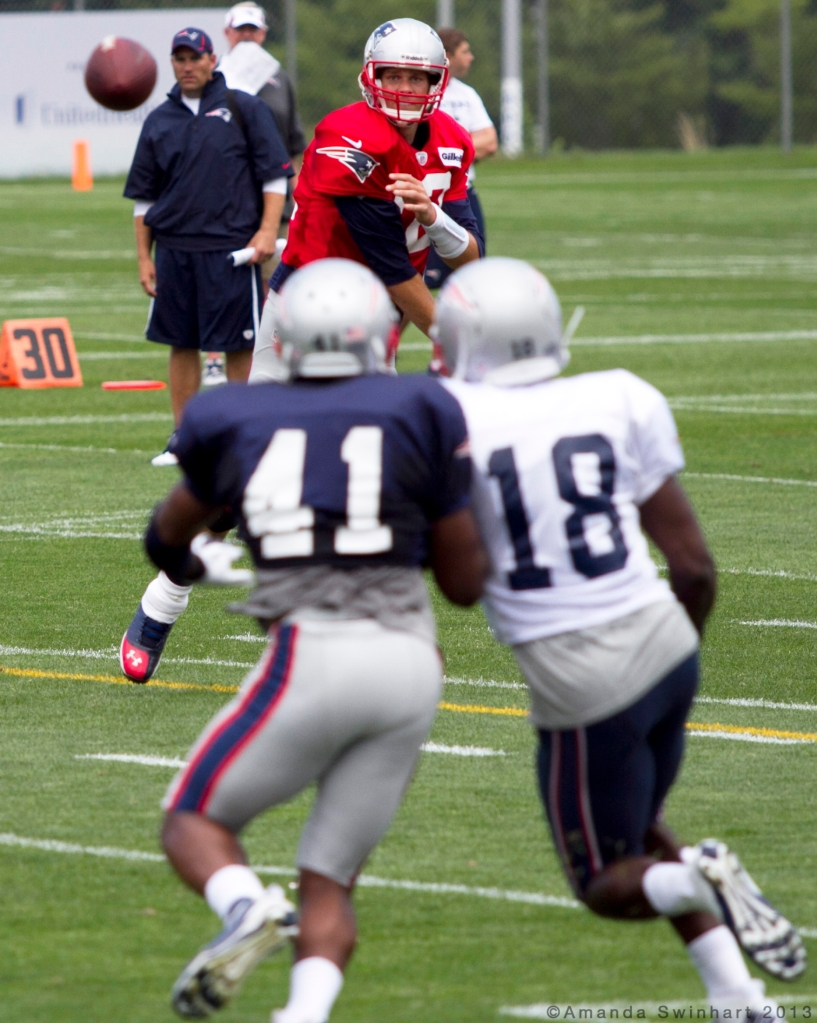 Foxborough, Mass., Aug. 1, 2013: New England Patriots starting quarterback Tom Brady throws a pass to wide receiver Matthew Slater (18) while rookie defensive back Justin Green (41) attempts to defend it during a training camp practice at Gillette Stadium. ©Amanda Swinhart 2013