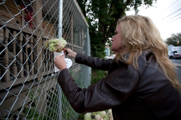 Blackstone, Mass., Sept. 14, 2014: Dawn adds a rosary, flowers, and a candle to a memorial in front of the home where three infants, along with several animals, were found dead on Sept. 10. Erika Murray, the homeowner, was arrested after police discovered the bodies inside the the vermin-infested home. Murray faces charges of fetal death concealment, witness intimidation and permitting substantial injury to a child. Police found four other children in the home who were taken into custody two weeks prior. The home was described as filthy inside, as it was littered with piles of trash and used diapers, as well as covered in feces. ©Amanda Swinhart