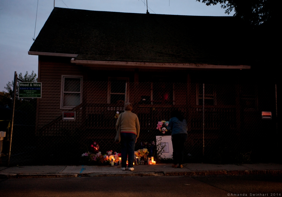 Blackstone, Mass., Sept. 14, 2014: As the sun sets, residents of Blackstone stand at a memorial in front of the home where three infants were found dead on Sept. 10, along with the remains of several animals. Erika Murray, the homeowner, was arrested after police discovered the bodies inside the the vermin-infested home. Murray faces charges of fetal death concealment, witness intimidation and permitting substantial injury to a child. Police found four other children in the home who were taken into custody two weeks prior. The home was described as filthy inside, as it was littered with piles of trash and used diapers, as well as covered in feces. ©Amanda Swinhart