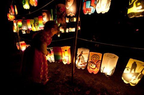 Jamaica Plain, Mass., Oct. 18, 2014: A child views lanterns for sale at the Jamaica Pond Lantern Parade, an event that has been taking place each fall since 1984. Parade goers create or purchase lanterns made from recycled soda bottles and colored tissue paper, and carry them as they journey around Jamaica Pond. Many children come dressed in their Halloween costumes.